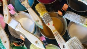 Natural bristle brushes are laying on top of round metal tins. The tins have different colours of molten wax inside. The tins are lined up on a black-topped pancake griddle.