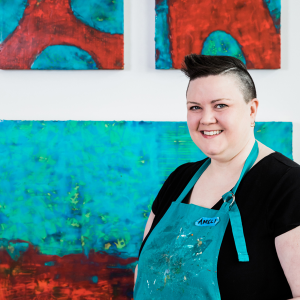 Amelia Kraemer is wearing a black t-shirt and a turquoise apron. She is standing in front of three of her paintings in the background. Her paintings are turquoise and red.